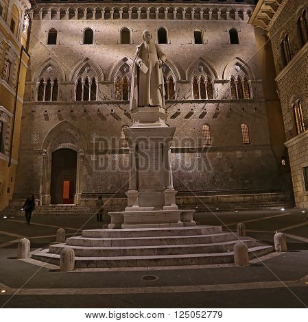 SIENA ITALY - MARCH 11 2016: Sallustio Bandini on Piazza Salimbeni at night Siena Tuscany - Italy.