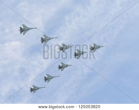 Moscow-May 9 2015: Eight powerful multipurpose heavy fighter gray-blue Su-30 is flying high in the sky at the Victory Day parade May 9 2015 Moscow Russia