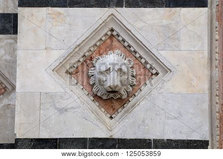 Siena - Head carved in marble on the facade of the Baptistery