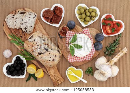 Healthy fresh food with olive bread and olives, camembert, fresh and sun dried tomatoes, herbs, garlic, oil and figs.