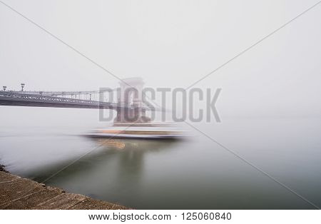 Chain Bridge over the Danube and a boat in Budapest, Hungary, in evening lights, on a foggy day. Shot from the Pest side of the Danube river