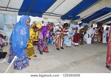 Abidjan, Ivory Coast- February 26, 2015: Women dance during a traditional wedding ceremony. Aligned all women perform the same movements which give harmony.