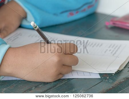 Thai student writing a test in exercise exams on old desk
