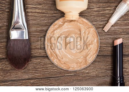 Close-up of flat makeup brush with liquid foundation squeezed out of tube, corrector and concealer pencil on dark wooden surface
