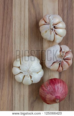 Artistic onion and garlic on wooden table.