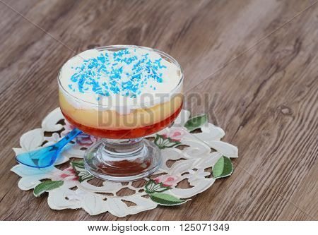 Traditional English trifle with blue sprinkles on wooden surface with copy space