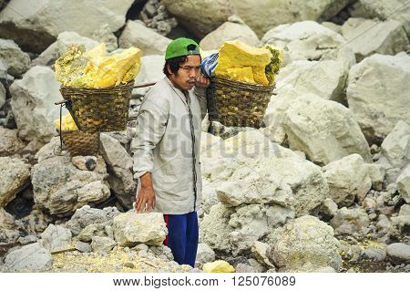 Ijen Crater, Indonesia - May 25, 2013: Sulfur miner carrying baskets with sulfur at Kawah Ijen volcano in East Java Indonesia.