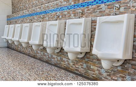 Closeup of white urinals in men's bathroom.