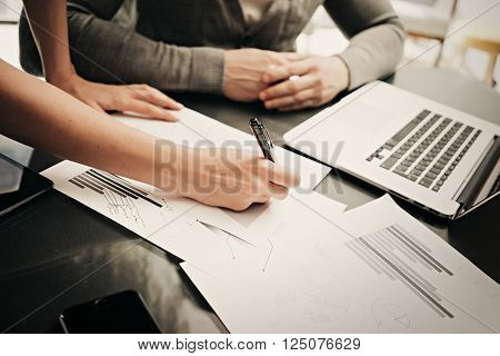 Business situation, meeting of financial analysts.Photo female hand showing document.Man listening to the report and using modern laptop.Working process modern office, discussion startup.