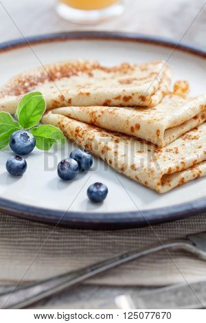 close up view of nice yummy crepes with berry on table