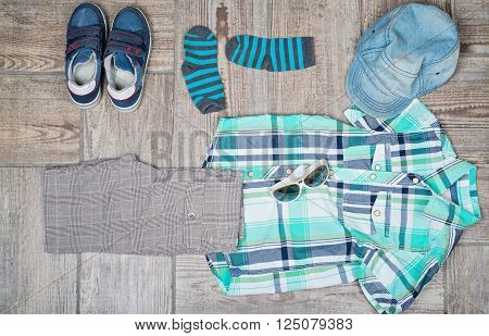 Boy's casual outfit on wood board background. Flat lay photography of boy's casual outfit. poster