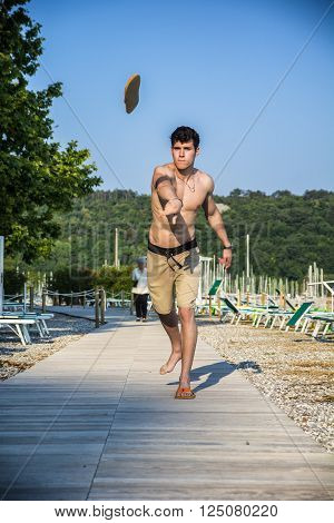 Attractive young shirtless athletic man standing at the beach on sundeck throwing loafer or flip-flop or shoe, wearing shorts, looking at camera