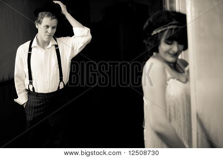 Attractive Young 1920's Guy Flirting With Young, Pretty Flapper Girl Outside Hotel Room.