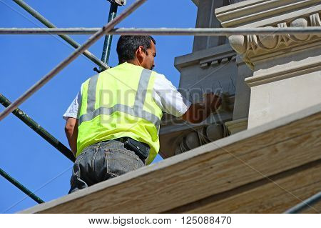BAKERSFIELD, CA - MARCH 13, 2016: An unidentified workman cleans and applies sealer to the restored masonry of an old building. The intricate designs had been covered with plaster for years.