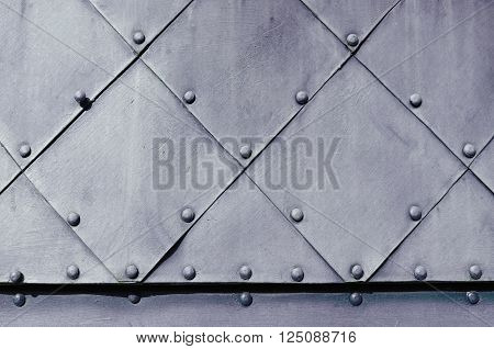 Metal grunge background - dark grey textured metallic superficies of old carved metal plates with small rivets above