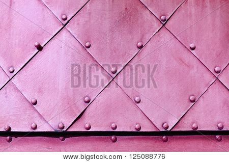 Metal grunge background in bright pink colors - textured steel superficies of old carved metal plates with small rivets above.