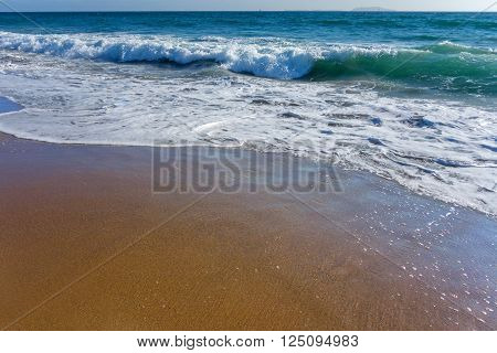 Waves with soapy suds coming from distant Channel Islands polish sands of Mandalay beach in Oxnard, , Ventura county, Southern California