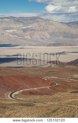 Winding road going down into Panamint Valley, passing through a red cinder cone, with cloud shadows on the valley floor.