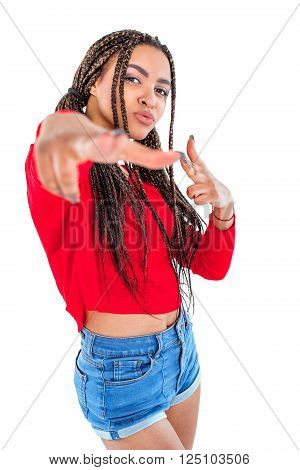 Funny picture of audacious african young woman. Girl with African braids looking at camera and making shooting gesture. Isolated background