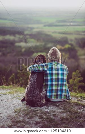 Woman and her dog posing outdoor. Girl loving and hugging tightly her dog and watching landscape.