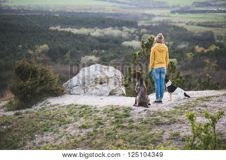 Woman and her dogs posing outdoor.