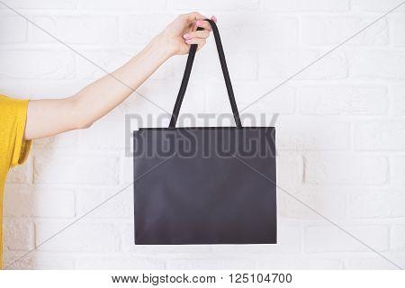 Closeup of female hand holding black shopping bag on white brick background. Mock up