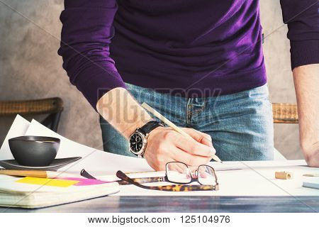 Frontview of man drawing on large paper on wooden table with coffee and other items