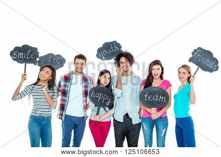 Studio shot of nice young multicultural friends. Beautiful people looking at camera, holding nameplates with different words and smiling. Isolated background