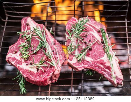 Rib eye steaks and grill with burning fire behind them.