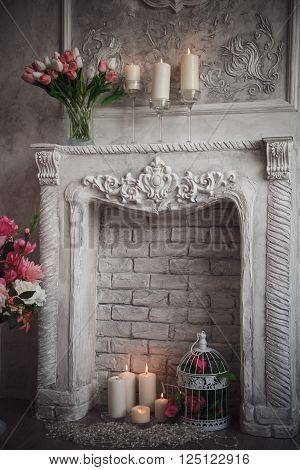 Interior with grey fretwork background, fireplace and flowers