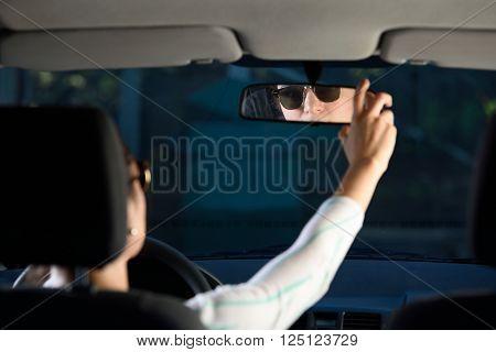 Woman Adjusting Rear Mirror