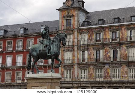Bronze equestrian statue of King Philip III and Casa de la Panaderia ( Bakery House ) on background Plaza Mayor Madrid Spain