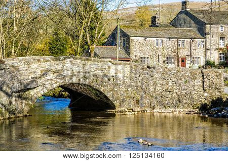 Stone bridge over a river in Malham village, Craven, Yorkshire, England.