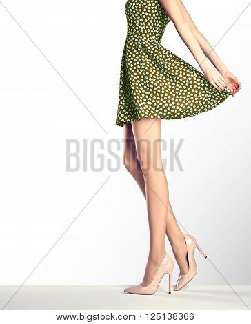 Woman in fashion vintage dress and high heels. Perfect female sexy long legs, stylish green skirt and summer glamour shoes. Unusual creative elegant walking out outfit, people.  Vintage, copy space