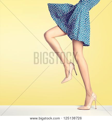 Woman long legs in fashion dress, high heels. Perfect female  sexy legs, stylish blue skirt and summer glamour shoes on yellow. Unusual creative elegant walking out outfit, people. Vintage, copy space