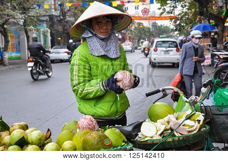December 2013. A woman in traditional straw hat sells fruit on the street in the center of Hanoi Vietnam.