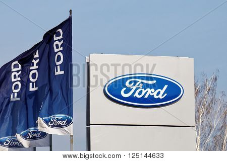 Ulyanovsk Russia - April 09 2016: Ford sign and flags near Ford car selling and service center.