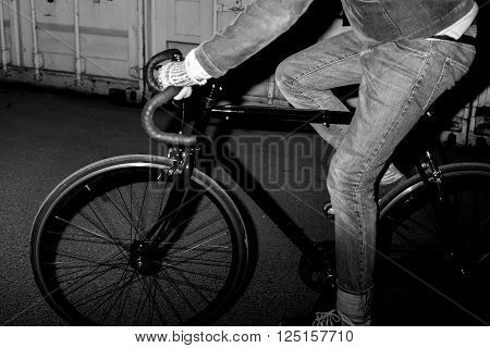 Fashionable urban dweller on fixed-gear bicycle at night. Black and white lifestyle poster