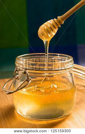 Acacia honey in a jar with honey stick