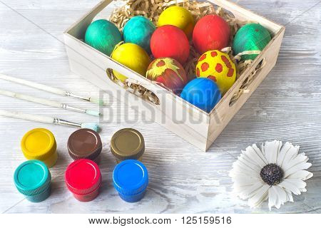 Easter colored eggs in a wooden box and paint on a light wooden background