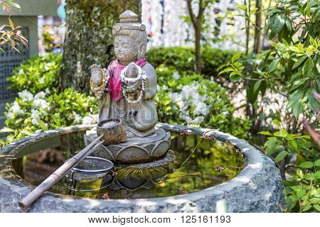 Itsukushima, Japan - April 27, 2014: A purification fountain in Daisho-in temple. At the entrance of Buddhist and Shinto temples in Japan, there is a fountain that people can use for purification.