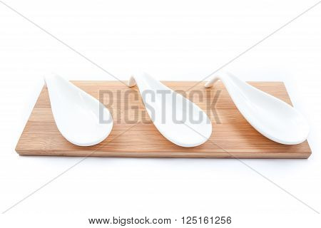 on a white background is stone spoons on an wooden board