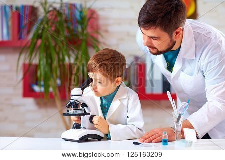 teacher helps kid to conduct experiment with microscope in school lab