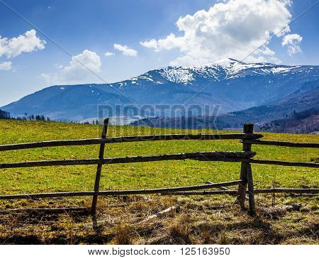fence on the rural meadow in mountain region in spring time