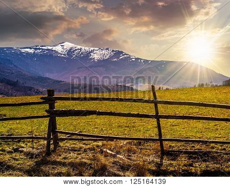 fence on the rural meadow in mountain region in spring time in evening light