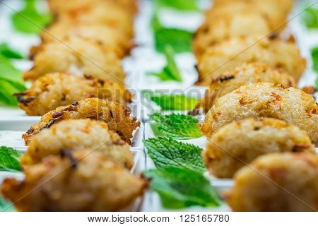 Closeup of breaded chicken nuggets and peppermint leaves