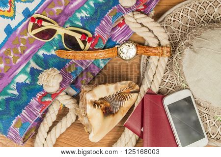 Going on vacation. Beach bag passport watch cell phone and glasses.