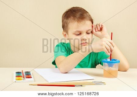Little boy in a green shirt going to paint colors