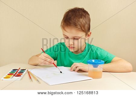 Beginner artist in a green shirt painting colors