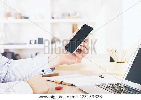 Sideview of male hand holding black smartphone in office